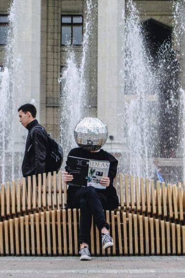 Mann mit Disko-Kugel auf dem Kopf - auf einer Bank sitzend - ein Magazin über innovative Ideen in der Hand
