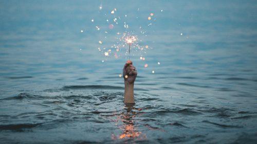 Hand mit Wunderkerze ragt aus Wasser heraus - Sinnbild für den letzten Funken Kreativität in einem Unternehmen, der aber auch bald zu erlöschen droht